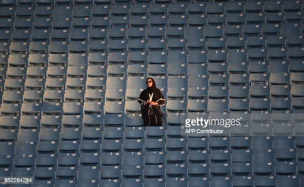 A Saudi woman arrives at a stadium to attend an event in the capital Riyadh on September 23 2017 commemorating the anniversary of the founding of the...