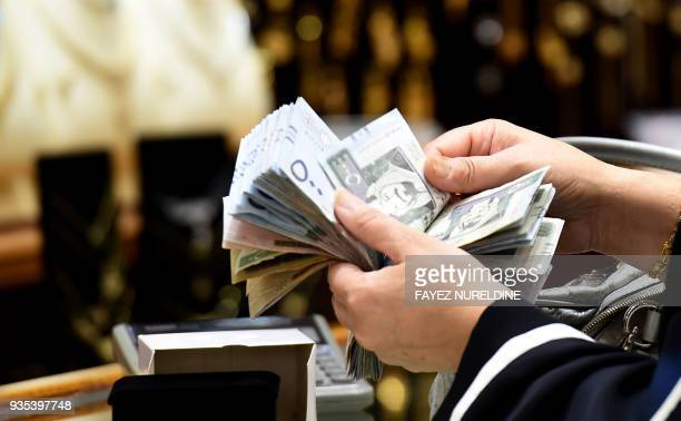 A Saudi woman counts banknotes as she makes a purchase at a jewellery shop in the Tiba gold market in the capital Riyadh on February 27 2018 The...