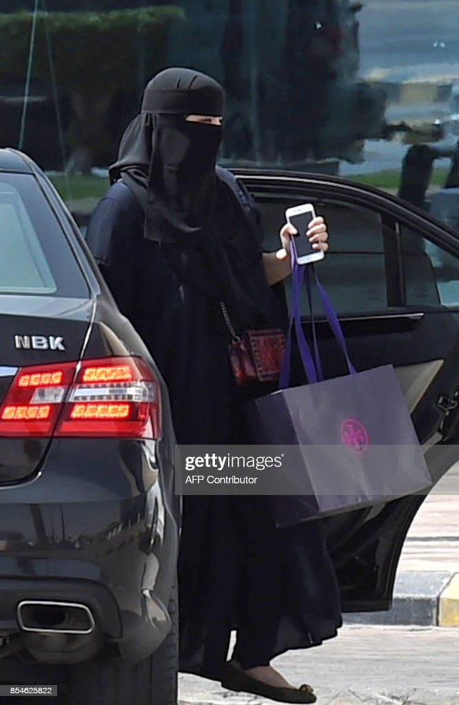 A Saudi woman disembarks from a car outside a mall in the Saudi capital Riyadh on September 27, 2017. Saudi Arabia will allow women to drive from next June, state media said on September 26, 2017 in a historic decision that makes the Gulf kingdom the last country in the world to permit women behind the wheel. The shock announcement comes after a years-long resistance from women's rights activists, some of whom were jailed for defying the ban on female driving. /
