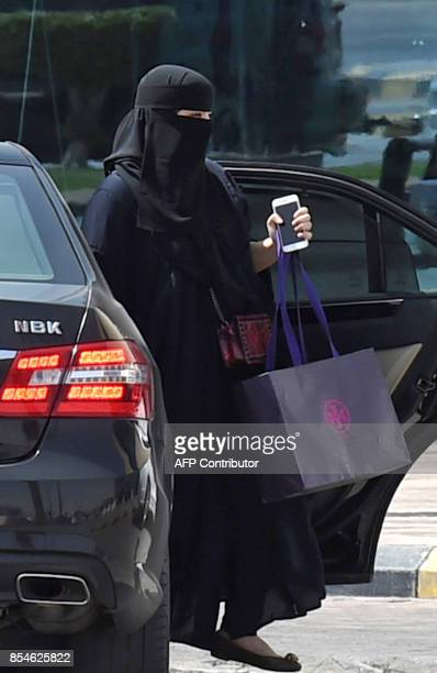 A Saudi woman disembarks from a car outside a mall in the Saudi capital Riyadh on September 27 2017 Saudi Arabia will allow women to drive from next...