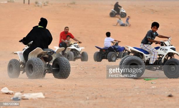 A Saudi woman drives an ATV with her family at Thumamah Park near Riyadh on April 5 2013 Saudi Arabia's religious police have lifted a ban on women...