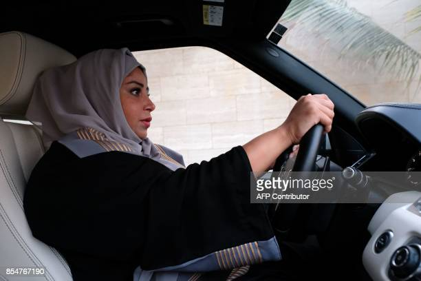 A Saudi woman drives her car along a street in the Saudi coastal city of Jeddah on September 27 2017 Saudi Arabia will allow women to drive from next...