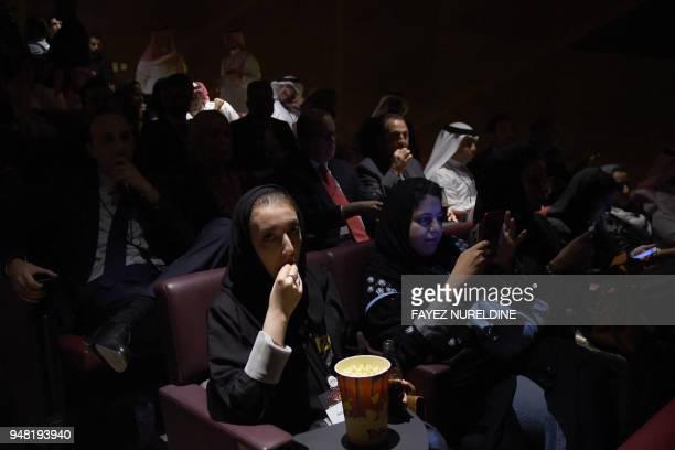 A Saudi woman eats popcorn at the AMC cinema during a test screening in Riyadh on April 18 2018 Blockbuster action flick 'Black Panther' play at a...