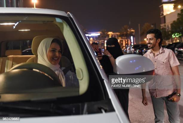 A Saudi woman films and shows support to Samar Almogren who drives her car through the streets of the Saudi capital Riyadh for the first time just...