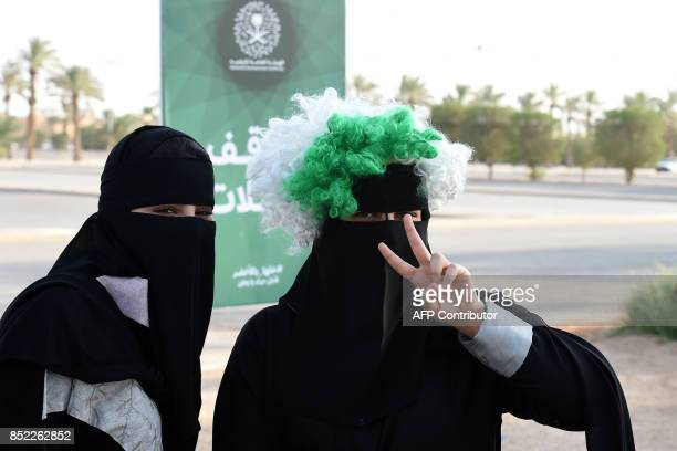 A Saudi woman flashes the victory gesture while wearing a coloured wig above her headdress as she arrives outside a stadium to attend an event in the...