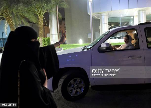 A Saudi woman flashes vsign to show support to Samar Almogren who is driving her car through the streets of the Saudi capital Riyadh for the first...