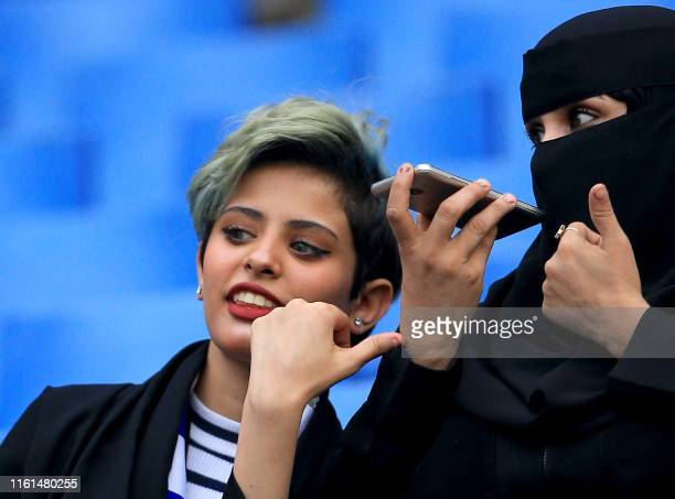 Saudi woman football fan records audio on her phone while waiting for her team in the stands ahead of the AFC Champions League play-off football...