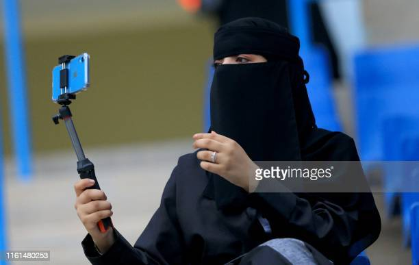 "Saudi woman football fan uses a ""selfie"" stick to film herself on her phone while waiting for her team in the stands ahead of the AFC Champions..."