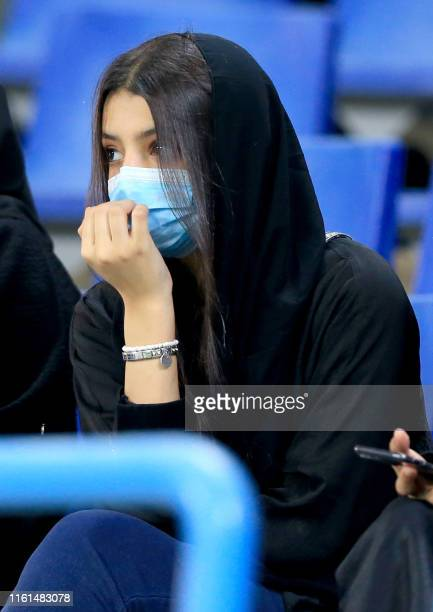Saudi woman football fan waits in the stands ahead of the AFC Champions League play-off football match between Saudi's al-Ahli and al-Hilal at King...
