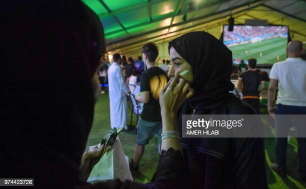 A Saudi woman football supporter has face paint applied to her a fan tent as the Russia 2018 World Cup Group A football match between Russia and...