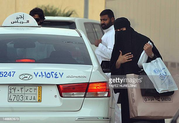 A Saudi woman gets into a taxi outside a shopping mall in Riyadh on June 22 2012 Saudi female activists have cancelled their plan to brave a driving...