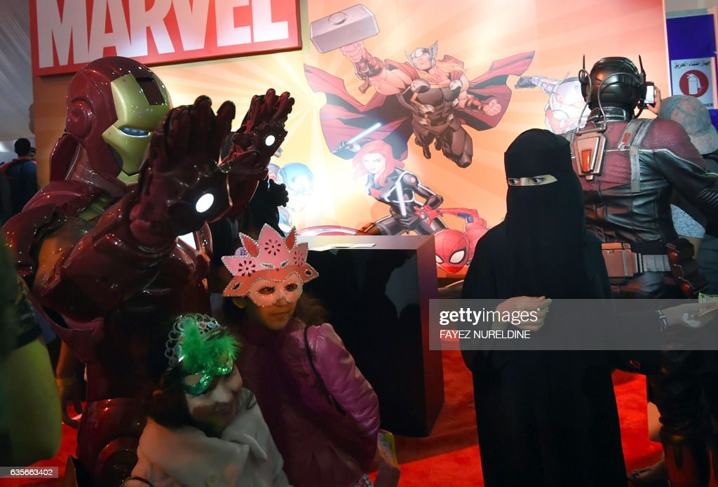 A Saudi woman looks on as children pose for a photo with a man dressed up as 'Iron Man' during the country's first ever Comic-Con event in the coastal city of Jeddah on February 16, 2017. The three-day festival of anime, pop art, video gaming and film-related events is part of a government initiative to bring more entertainment to Saudi Arabia which bans alcohol, public cinemas and theatre. / AFP / FAYEZ