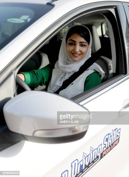 A Saudi woman poses for a photo as she has a driving lesson in Jeddah on March 7 2018 Saudi Arabia's historic decision in September 2017 to allow...