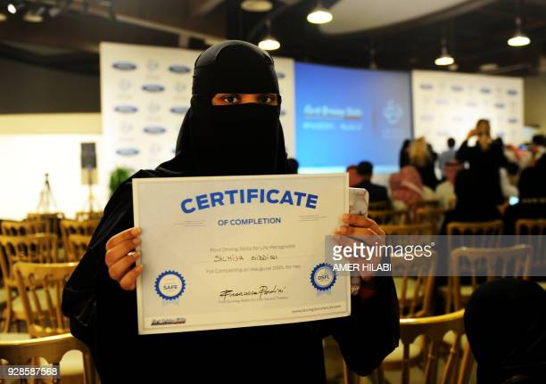 A Saudi woman poses for a photo with a certificate after completing a driving course in Jeddah on March 7 2018 Saudi Arabia's historic decision in...
