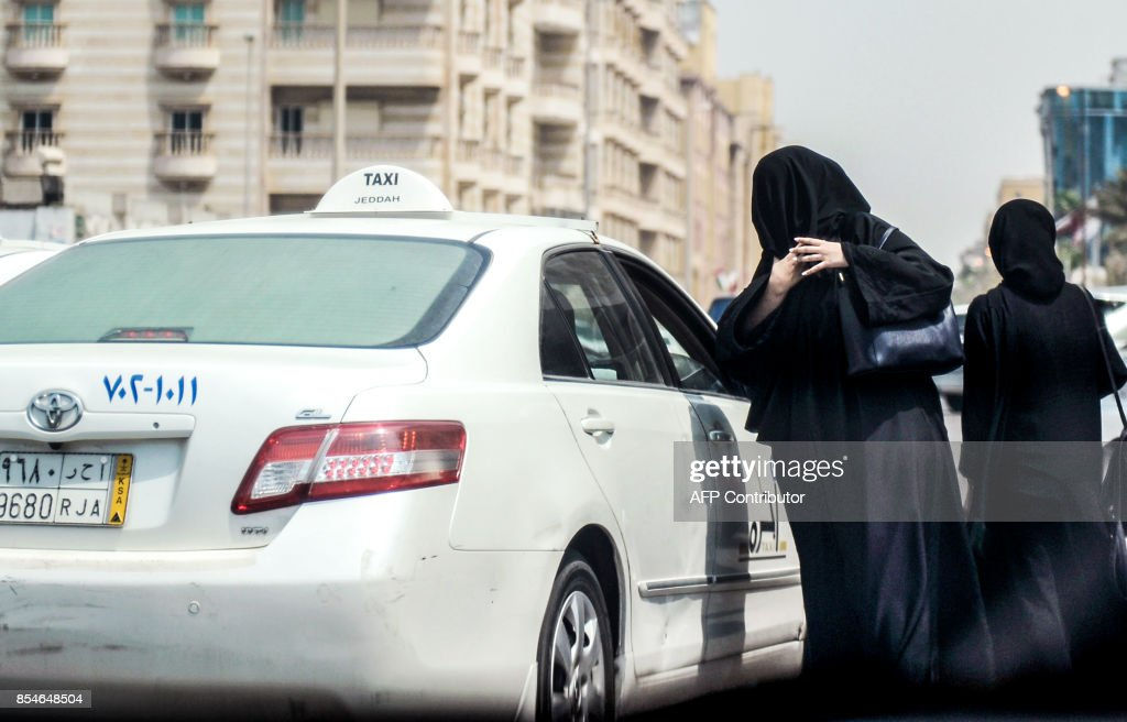 A Saudi woman prepares to get into a taxi on a main street in the Saudi coastal city of Jeddah on September 27, 2017. Saudi Arabia will allow women to drive from next June, state media said on September 26, 2017 in a historic decision that makes the Gulf kingdom the last country in the world to permit women behind the wheel. The shock announcement comes after a years-long resistance from women's rights activists, some of whom were jailed for defying the ban on female driving. /