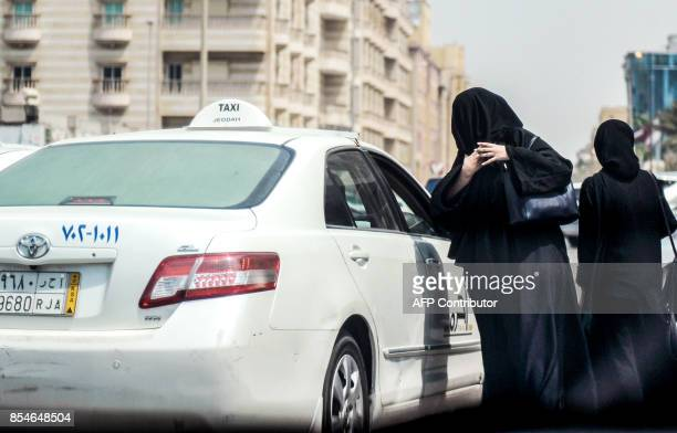 A Saudi woman prepares to get into a taxi on a main street in the Saudi coastal city of Jeddah on September 27 2017 Saudi Arabia will allow women to...