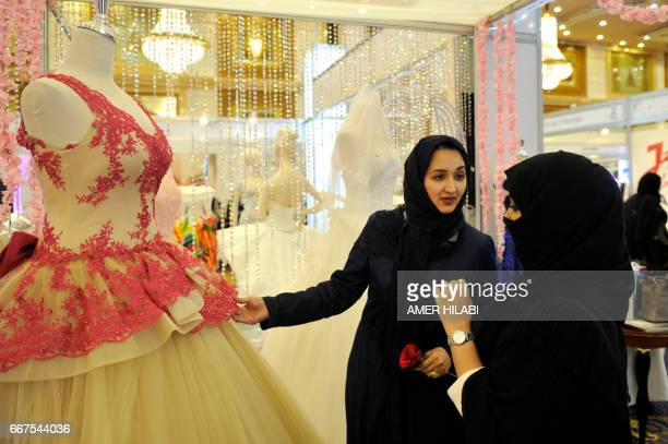 A Saudi woman shows wedding dresses to women at a bridal expo on April 11 in the Red Sea city of Jeddah / AFP PHOTO / Amer HILABI