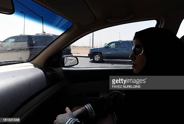 A Saudi woman sits in a vehicle as a passenger on September 22 2013 in Riyadh Saudi women activists have called for a new day of defiance next month...