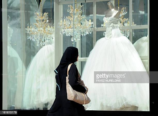 Saudi woman walks past wedding dresses displayed in a shop window on February 4 2013 at a mall in the Saudi capital Riyadh Websites offering services...