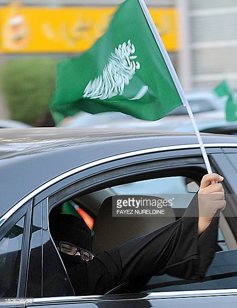 A Saudi woman waves her national flag during celebrations marking the 82nd Saudi National Day in the desert kingdom's capital Riyadh on September 23...