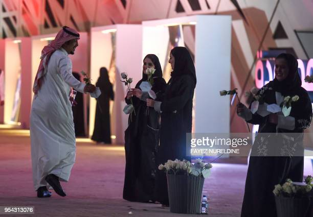 Saudi women distribute flowers to incoming attendees of the Quality of Life Program 2020 conference in the capital Riyadh on May 3 2018 The program...