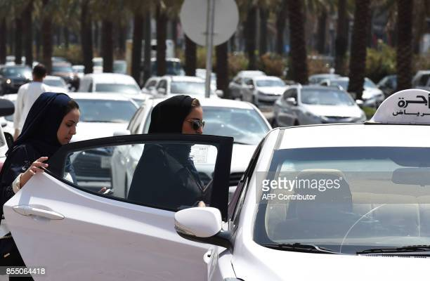 Saudi women get into a taxi at a street in the Saudi capital Riyadh on September 28 2017 Saudi Arabia will allow women to drive from June 2018 state...