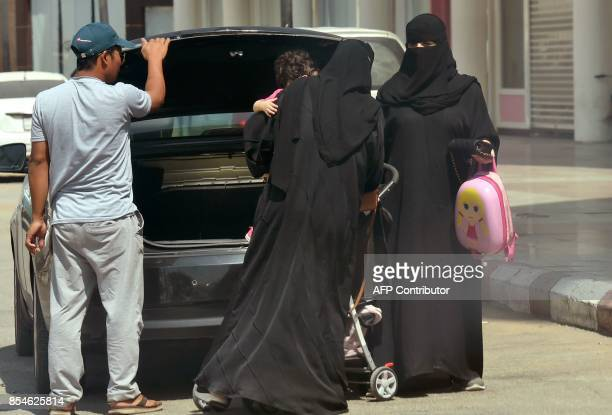 Saudi women take out an infant trolley from the boot of a car outside a mall in the Saudi capital Riyadh on September 27 2017 Saudi Arabia will allow...