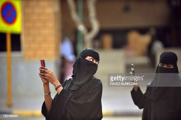Saudi women take pictures with their mobile phones after the end of a prayer performed on the first day of Eid alFitr in the great mosque in the old...