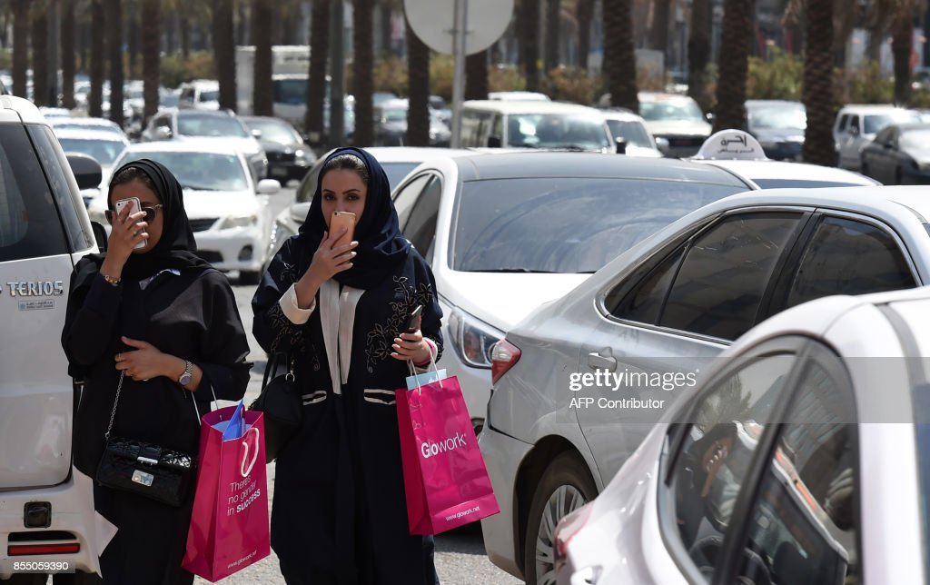 Saudi women walk amidst vehicles at a street in the Saudi capital Riyadh, on September 28, 2017. Saudi Arabia will allow women to drive from June 2018, state media said on September 26, 2017 in a historic decision that makes the Gulf kingdom the last country in the world to permit women behind the wheel. The shock announcement comes after a years-long resistance from women's rights activists, some of whom were jailed for defying the ban on female driving. /
