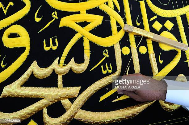 A Saudi worker sews Islamic calligraphy in gold thread on a drape to cover the Kaaba at the Kiswa factory in the holy city of Mecca on November 8...