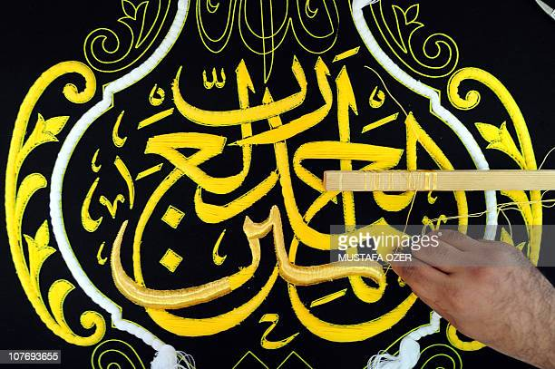 A Saudi worker stiches Islamic calligraphy in gold thread on a silk drape to cover the Kaaba at the Kiswa factory in the holy city of Mecca on...