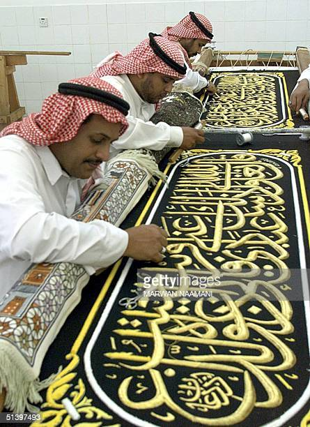 Saudi workers sew in Mecca 08 March 2000 verses of the Koran with golden threads on a of black cloth that will later cover the Kaaba Tradition has it...