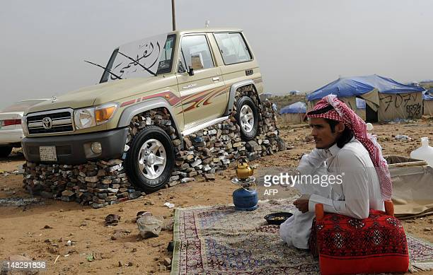 A Saudi youth sits nex to his sport utility vehicle lifted with stones and bricks in the tourist area of alHabla 50km south of the city of Abha in...