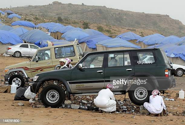 Saudi youths lift their sport utility vehicle with stones and bricks in the tourist area of alHabla 50km south of the city of Abha in the southern...