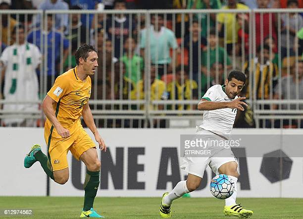 Saudi's Abdulmalek AlKhaibri dribbles past Australia's Mark Milligan during the 2018 FIFA World Cup Qualifiers match between Saudi Arabia and...