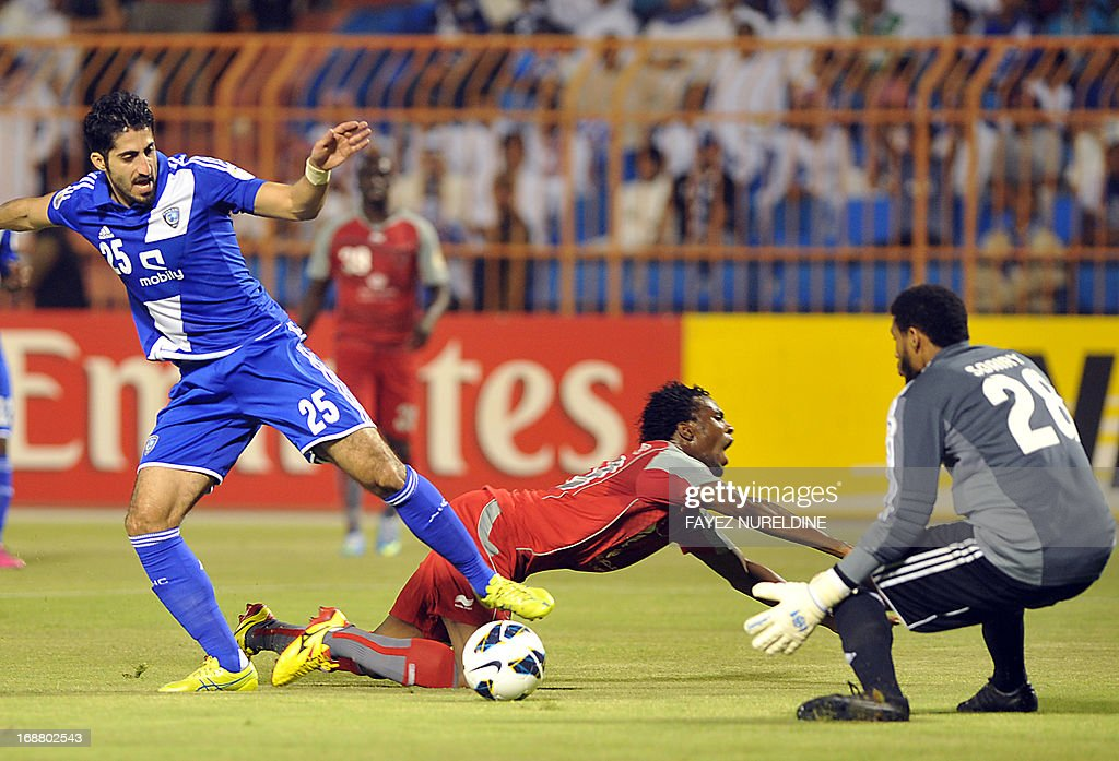 Saudi's Al Hilal player Almarshadi (L) controls the ball as Qatar's Lekhwiya Ismail Mohamad (C) falls down during their AFC Champions League football match on May 15, 2013 at the Prince Faisal bin ...