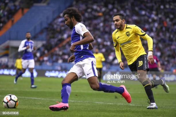 Saudi's AlHilal Mohammad AlShalhoub vies for the ball against AlIttihad's player in the Saudi Pro League football match at the King Fahd...