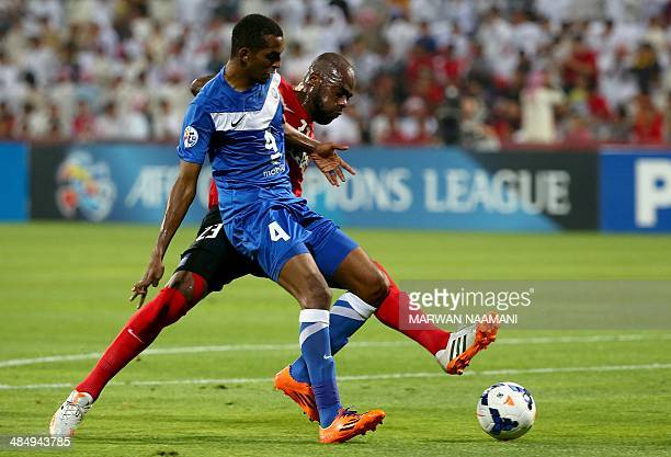 Saudi's Al-Hilal player Abdulla al-Dossary fights for the ball against UAE's Al-Ahli Brazilian player Grafite during their AFC Champions League Group...