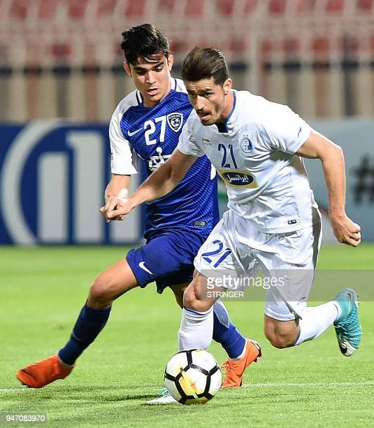 Saudi's alHilal player Achraf Bencharki vies for the ball against Iran's Esteqlal club player Vouria Ghafouri during the AFC Champions League...