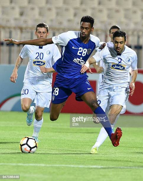 Saudi's alHilal player Mohammed Kanoo vies for the ball against Iran's Esteqlal club players Server Djeparov and Khosro Heydari during the AFC...