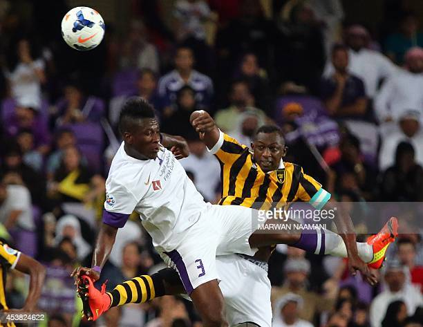 Saudi's AlIttihad defender Osama AlMuwallad fights for a header with UAE's AlAin's forward Asamoah Gyan during their AFC Champions League football...