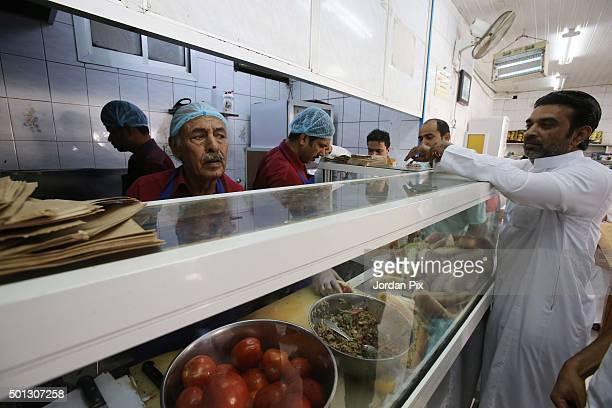 Saudis arrive to buy take away snacks at the AlAtlal cafeteria on December 12 2015 in Jeddah Saudi Arabia AlAtlal is a tiny cafeteria in the centre...