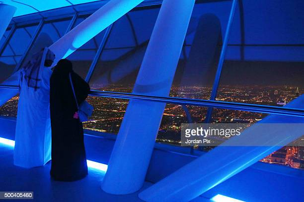 Saudis enjoy looking out over the skyline view of the city from the 99th floor the viewing floor at The Kingdom tower on December 7 2015 in Riyadh...