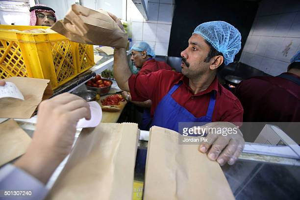 Saudis make take away snacks at the AlAtlal cafeteria on December 12 2015 in Jeddah Saudi Arabia AlAtlal is a tiny cafeteria in the centre of the...