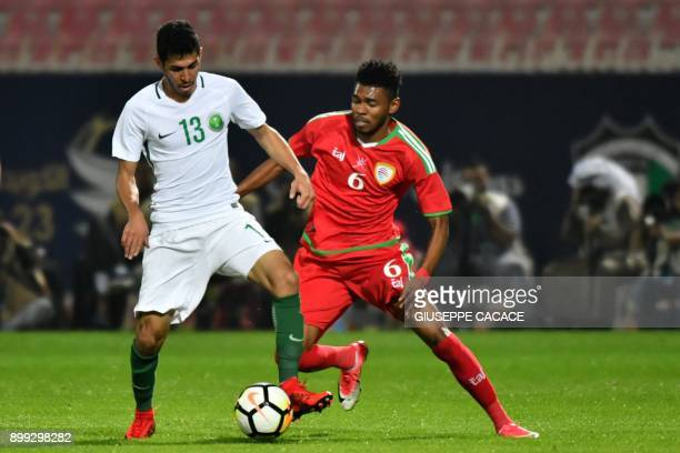 Saudi's Sultan alGhanam fights for the ball against Oman's Raed Ibrahim Saleh during the 2017 Gulf Cup of Nations football match between Saudi Arbia...