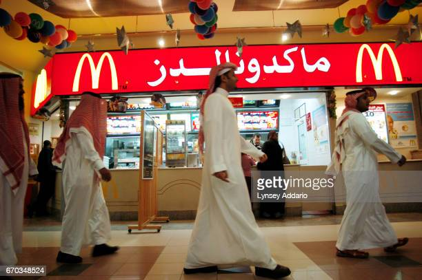 Saudis walk past McDonald's Restaurant in the Kingdom mall in Riyadh Saudi Arabia December 2003