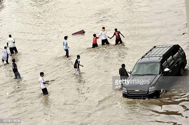 Saudis walk through a flooded street following heavy rain in the Red Sea port city of Jeddah on December 30 2010 AFP PHOTO/AMER HILABI