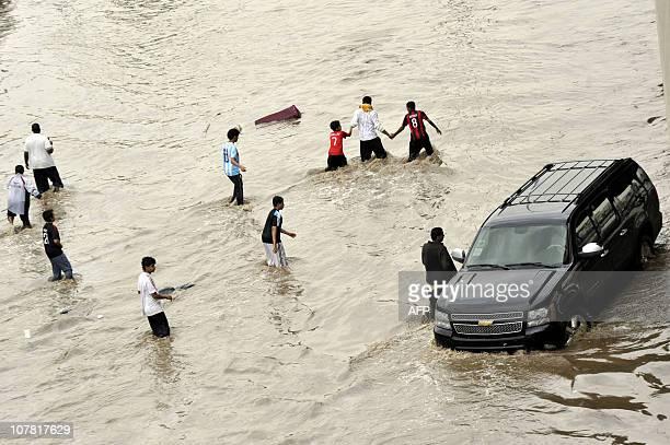 Saudis walk through a flooded street following heavy rain in the Red Sea port city of Jeddah on December 30 2010 AFP PHOTO/AMER HILABI