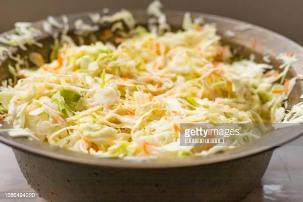 sauerkraut fermentation in copper basin bowl. cut white cabbage fermented by lactic acid bacteria - zuurkool stockfoto's en -beelden