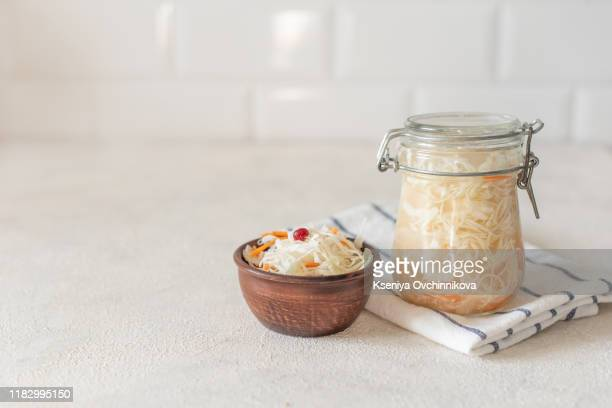 sauerkraut in glass mason jar. pickling cabbage at home on table. the best natural probiotic. homemade kraut., copy space for text - fermenting stock pictures, royalty-free photos & images